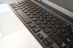 Silver laptop computer keyboard with black keys close up