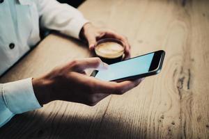 mano femenina con teléfono inteligente y sosteniendo una taza de foto