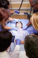 equipo médico trabajando en paciente en sala de emergencia foto