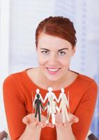 Beautiful Businesswoman Holding Team Of Paper People In Office photo
