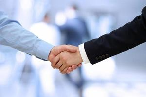 Image of a firm handshake  between two colleagues in office