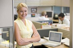 Smiling woman with arms crossed standing at the office