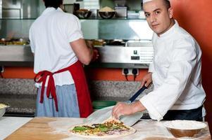 chef-kok die laatste aanraking geeft aan plantaardige pizza