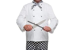 A chef wearing a white coat and sharpening knives