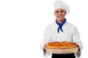 jovem padeiro detém um pão na tábua de pão