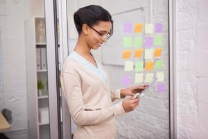 Empresaria sonriendo mientras toca una tableta foto