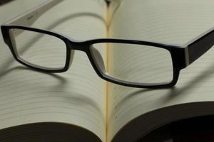 bloco de notas e óculos