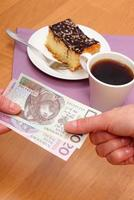 Paying for cheesecake and coffee in the cafe, finance concept