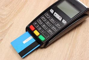 Payment terminal with credit card on desk, finance concept photo
