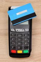 Payment terminal with contactless credit card on desk, finance concept photo