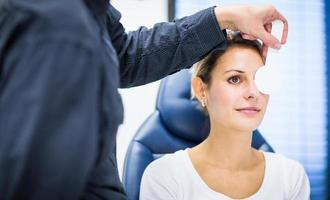 Pretty young woman having her eyes examined by optometrics photo