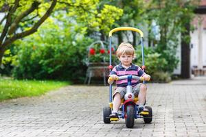 Little toddler driving tricycle or bicycle in home garden photo