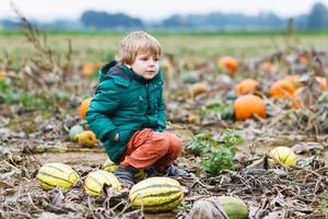 Toddler boy having fun sitting on huge  halloween pumpkin