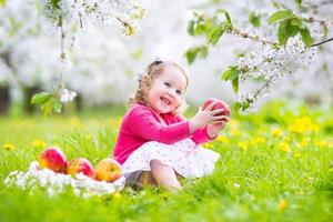 Adorable toddler girl eating apple in a blooming garden