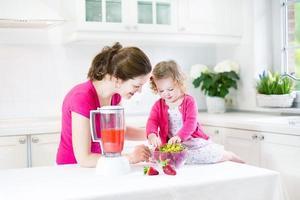 linda niña pequeña y hermosa madre haciendo jugo de fruta fresca foto