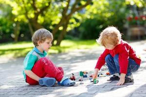 Two little kid boys playing with car toys photo
