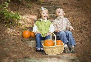 Hermano y hermana niños sentados en escalones de madera con calabazas