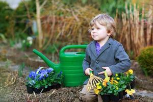 Little boy gardening and planting flowers in garden photo