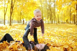 mother and the kid walk in autumn park photo