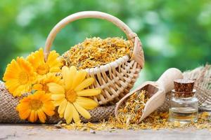 Marigold flowers, basket with dried plants and oil bottle