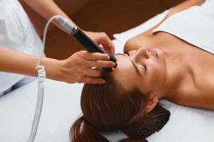 cuidados com a pele do rosto. mulher no spa de beleza, recebendo um tratamento
