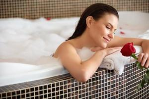 Beautiful Woman Relaxing in Bath With Rose. Body Care