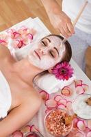 mujer recibiendo máscara facial en spa studio foto