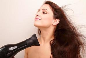 hermosa mujer secando el cabello largo y sano con emoción natural de alegría foto