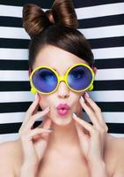 Attractive surprised young woman wearing sunglasses on striped background