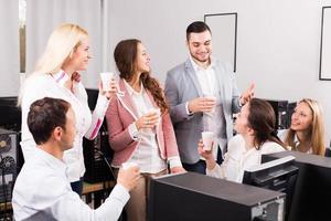 Happy employees and manager celebrating photo