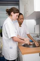 dos empleados se lavan las manos en un fregadero