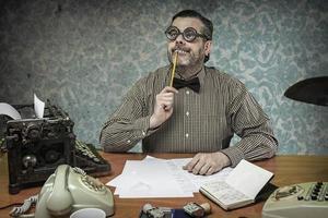 empleado de oficina pensativo con un lápiz en la boca, años 60
