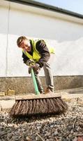 jovem trabalhador manual varre um caminho