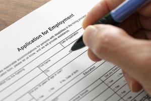 Close-up of a hand filling out a job application