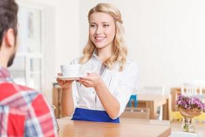 Smiling waitress giving cup of coffee