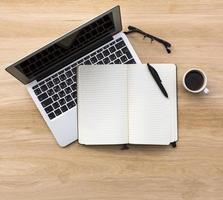 laptop, notebook com caneta, óculos e xícara de café