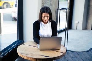 atractiva empresaria usando laptop en café foto