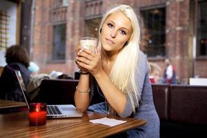 mujer joven con laptop en café foto