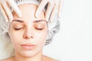 Woman in spa salon receiving face treatment with facial cream photo