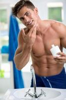 Young man applying after shave photo