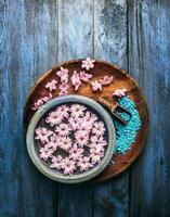 bowl with pink flowers in water,  scoop  of sea salt