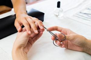 Manicurist trimming a clients cuticles