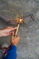 worker welding metal exhaust pipe with sparks photo