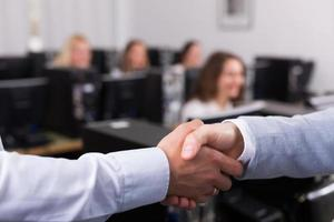 Manager shaking hand of employee