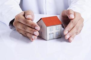 papel de la casa de protección de manos para concepto de préstamos hipotecarios foto