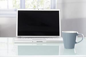 Closeup photo of laptop and tea mug