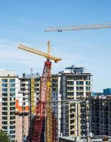 High Rise Construction with Red and Yellow Cranes photo