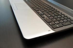 Silver laptop computer with black keyboard close-up on a table