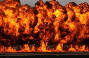 grande explosão com enormes chamas laranja no céu