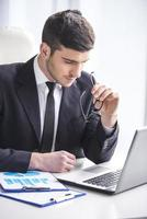 Man in suit holding glasses in hand looking at laptop